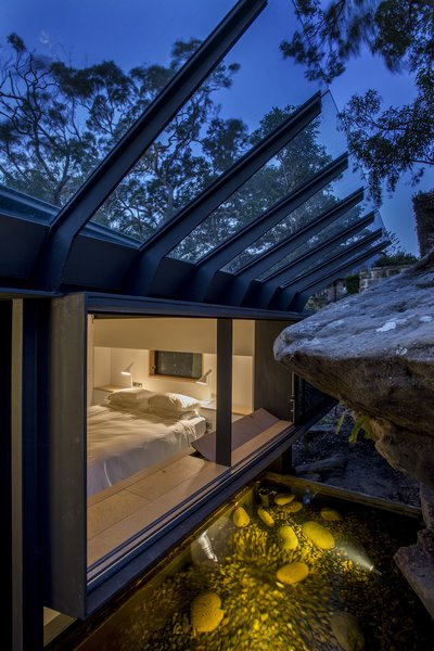 The principle bedroom windows embrace the sandstone rock face. A sloped glass roof shields rain.
