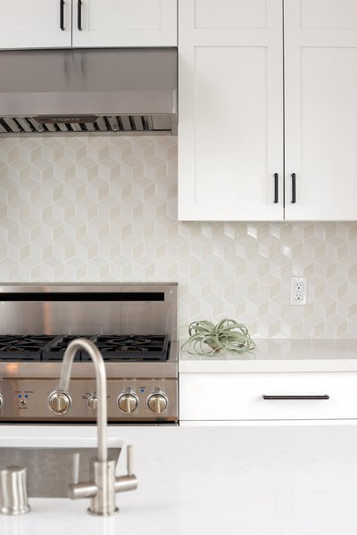 Fresh white kitchen with warm wood wrapped island, black cabinet pulls and Dwell patterns Heath tile backsplash . Photo 3 of Chenery Street Remodel modern home