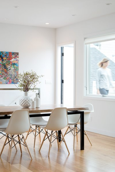 The dining area is positioned off of the kitchen and next to the living area to create open, flexible space. Behind the dining table, open stairs lead down to the family room on the ground floor. A small roof deck is also accessible off the dining area. Photo 6 of Chenery Street Remodel modern home