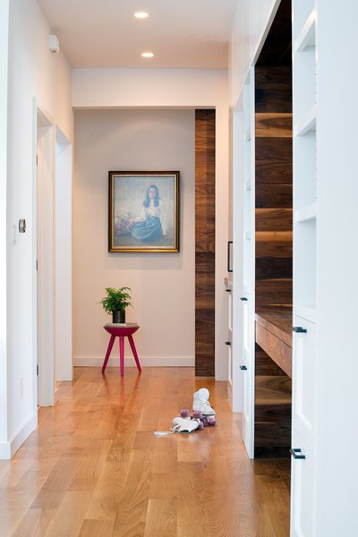 A full wall of built-in storage cabinets accented with walnut and oil-rubbed bronze hardware. A large walnut sliding barn door leads to the master suite and office areas. Photo 5 of Chenery Street Remodel modern home