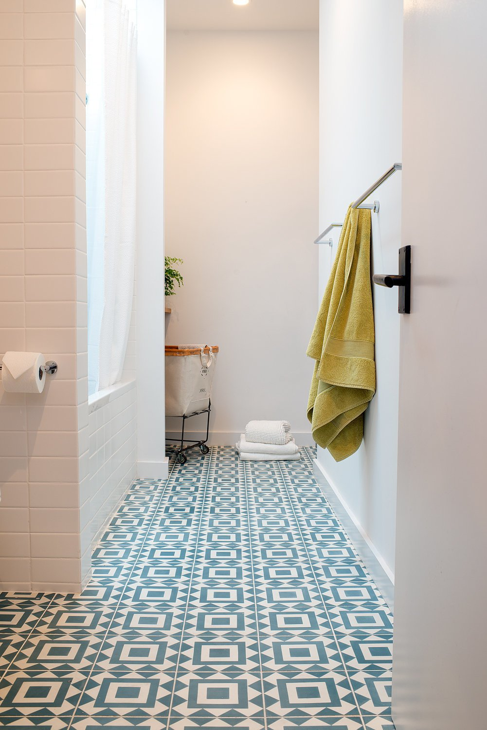 An existing lightwell was filled-in to create space for a concealed laundry area at the rear of the main bathroom. Soft natural light pours in from the skylight over the tub. Tagged: Bath Room, Ceramic Tile Floor, and Subway Tile Wall.  Chenery Street Remodel by SF Design Build