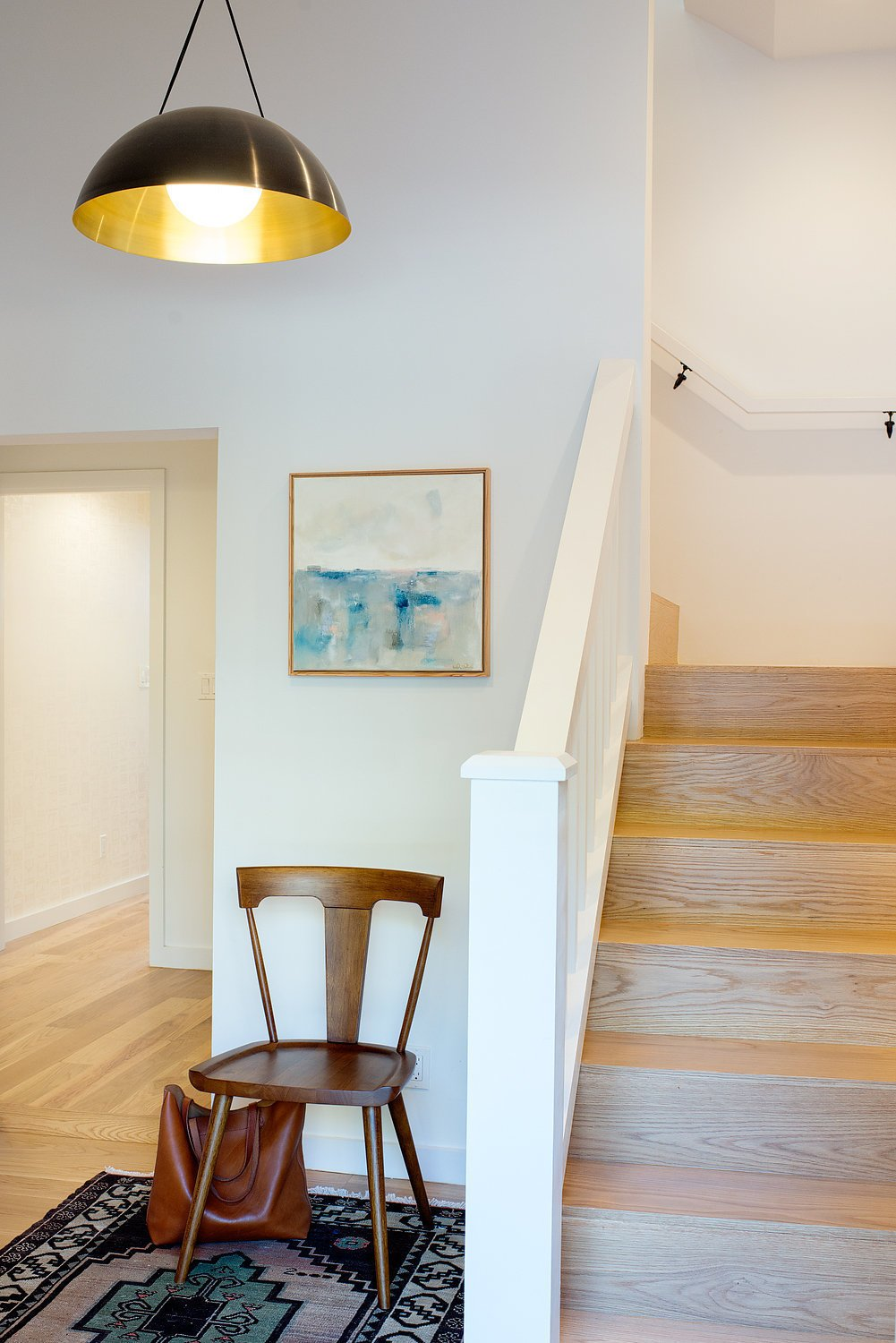 The ground floor entry was once a mix and match of different flooring materials and floor level heights. All the details were though out to create a functional, one-level space with new white oak flooring and stair treads to match the upstairs rooms.