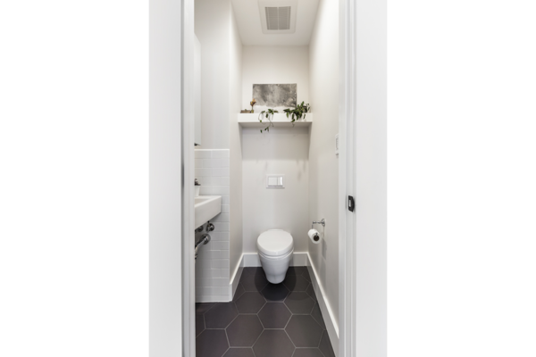 The new powder room includes a wall-hung Toto toilet and wall-hung Duravit sink, white subway wall tiles and charcoal gray medium hex floor tiles to create a functional space that feels larger than it is.