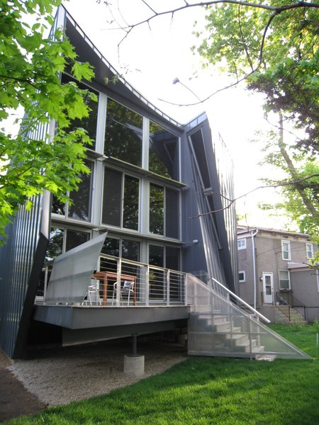 """SOUTH ELEVATION looking NE: elevated living space to meet code. passive solar elements…¼"""" bent aluminum plate sunshades, overhang. the railing system uses aluminium angle & tube armature, perforated aluminum panels, stainless steel cable. 1 x 6 trex decking on the walking surfaces. the """"slit glazing"""" resembling a pair of """"tweezers"""" grabs the late PM light.                   Photo 4 of metalHOUSE(2) modern home"""