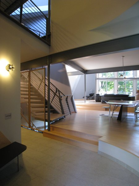 """entry hall looking S: dining room w/living room beyond. steel, single stringer cantilever stair. perforated aluminum screen. 12 x 24 porcelain ceramic tile, 2 ¼"""" oak strip flooring from renewable forests. Photo 6 of metalHOUSE(2) modern home"""