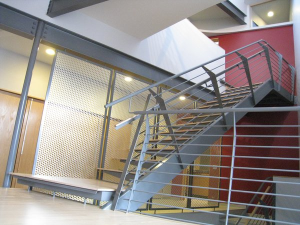 """looking NE from the dining room into the solar chimney: steel tube single stringer. ¼"""" folded steel cantilevered brackets form the treads/risers. ¾"""" oak applied wearing surface. ¼"""" steel verticals, ½"""" rod balusters w/1 ½"""" steel top tube rail. steel angle frame w/perforated aluminum infill screen, entry hall beyond. transom at upper tight is in the hall bath shower. Photo 13 of metalHOUSE(2) modern home"""