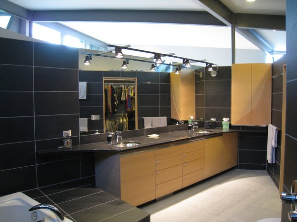 looking SW from the MBR bath: horizontal grain rift oak cabinets w/wood boxes. black granite tops, bracketed tracklighting. 12 x 24 porcelain ceramic tile.     Photo 16 of metalHOUSE(2) modern home