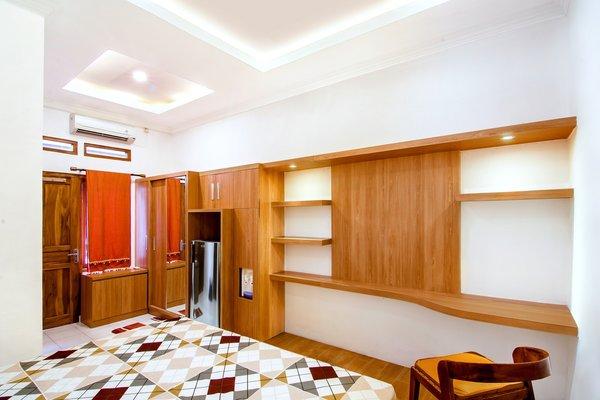 Modern home with bedroom, bed, chair, dresser, bookcase, wardrobe, storage, ceiling lighting, shelves, table lighting, and ceramic tile floor. Photo 5 of Prawirotaman Street
