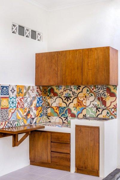Modern home with kitchen, tile counter, wood cabinet, ceramic tile floor, ceramic tile backsplashe, concrete counter, dishwasher, ceiling lighting, range hood, and drop in sink. Photo 3 of Prawirotaman Street