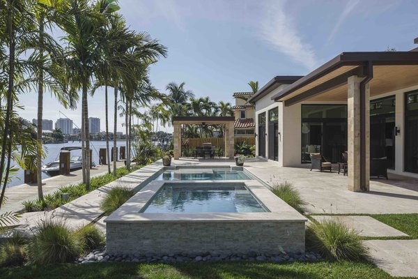 Modern home with outdoor, back yard, trees, grass, flowers, gardens, shrubs, stone patio, porch, deck, hardscapes, pavers patio, porch, deck, large pool, and landscape lighting. Photo  of Sunrise Key Residence