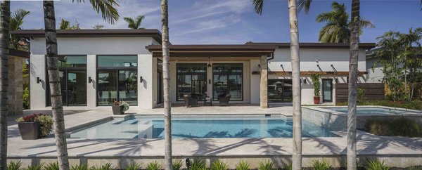Modern home with outdoor, back yard, pavers patio, porch, deck, large pool, and hardscapes. Photo 4 of Sunrise Key Residence