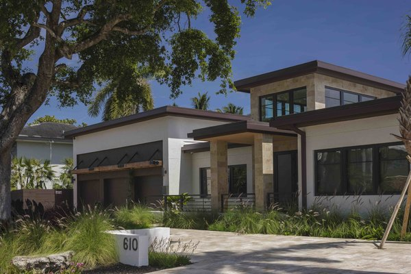 Modern home with outdoor, front yard, grass, horizontal fence, wood fence, and metal fence. Photo 5 of Sunrise Key Residence