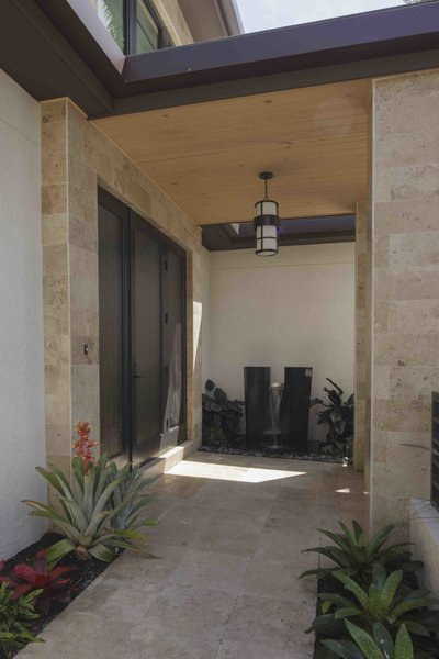 Modern home with outdoor, front yard, hanging lighting, hardscapes, and pavers patio, porch, deck. Photo 7 of Sunrise Key Residence