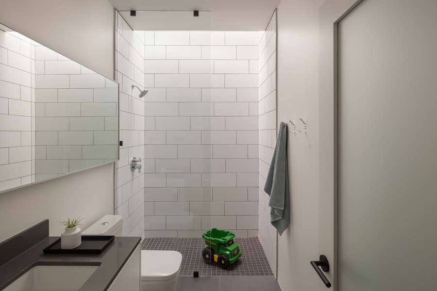 Bathroom Tagged: Bath Room, Engineered Quartz Counter, Porcelain Tile Floor, Undermount Sink, Open Shower, Subway Tile Wall, and One Piece Toilet.  Pavilion Haus by studioMET architects