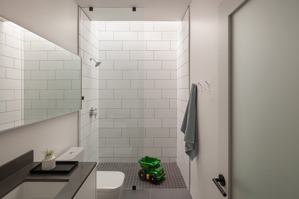 Modern home with bath room, engineered quartz counter, porcelain tile floor, undermount sink, open shower, subway tile wall, and one piece toilet. Bathroom Photo 15 of Pavilion Haus