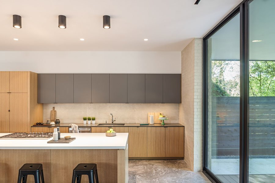Kitchen Tagged: Kitchen, Engineered Quartz Counter, Wood Cabinet, Concrete Floor, Recessed Lighting, Accent Lighting, Porcelain Tile Backsplashe, Cooktops, and Undermount Sink.  Pavilion Haus by studioMET architects