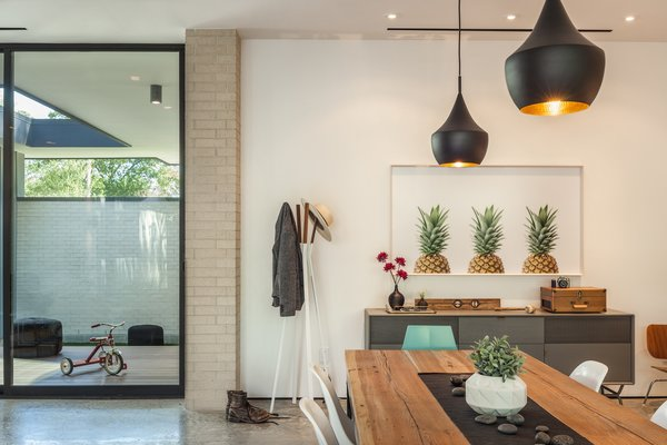 Modern home with dining room, chair, table, ceiling lighting, accent lighting, recessed lighting, pendant lighting, and concrete floor. Dining Room Photo 6 of Pavilion Haus