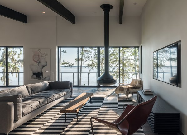 Modern home with living room and hanging fireplace. Photo 3 of Lakefront
