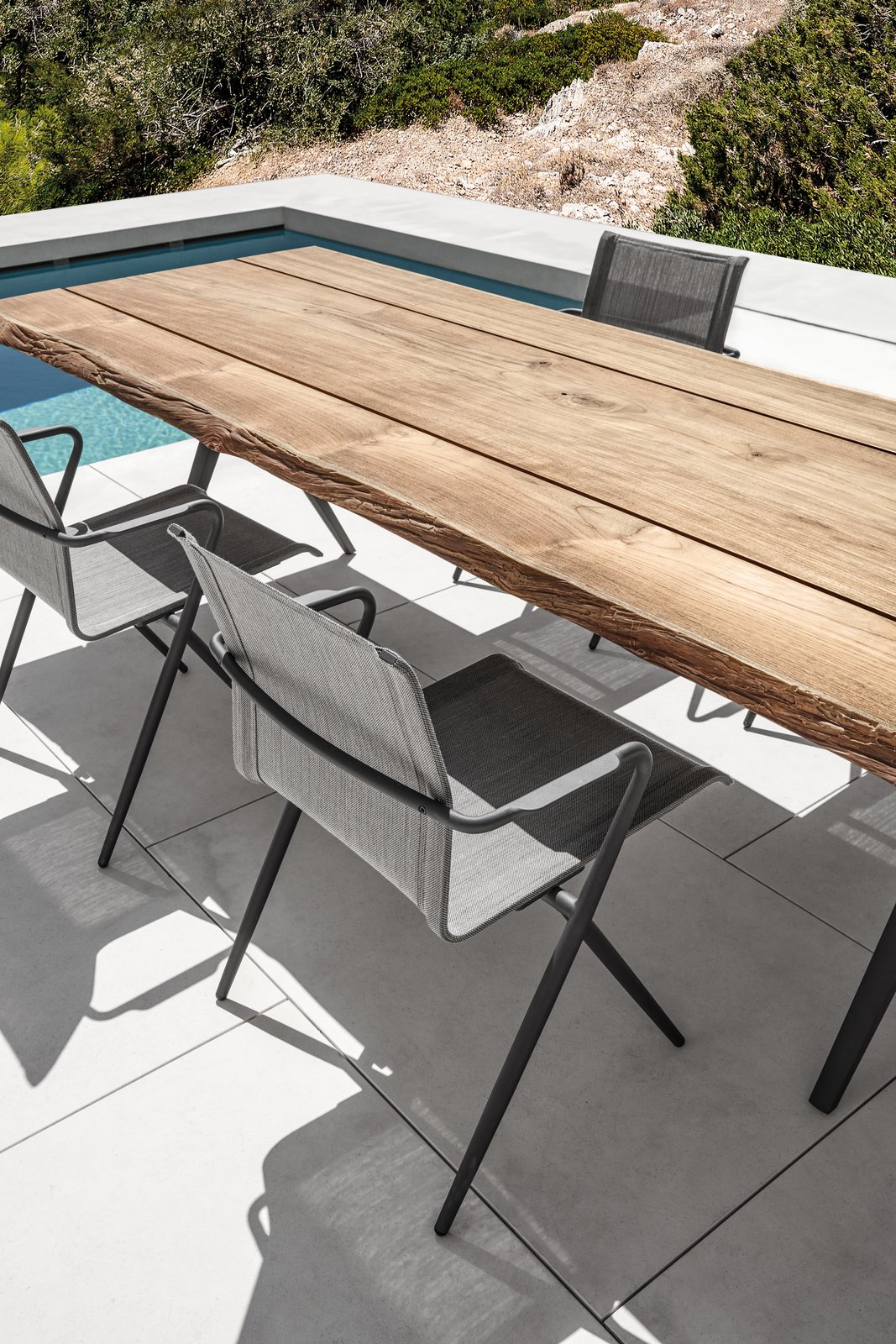 Stackable Ryder dining chair in a dark version in contrast to the limited edition teak table Split Raw. Tagged: Chair, Table, Outdoor, Large Pools, Tubs, Shower, Small Pools, Tubs, Shower, Swimming Pools, Tubs, Shower, Large Patio, Porch, Deck, Hardscapes, Small Patio, Porch, Deck, Back Yard, and Tile Patio, Porch, Deck.  Dining Chairs by Gloster Furniture