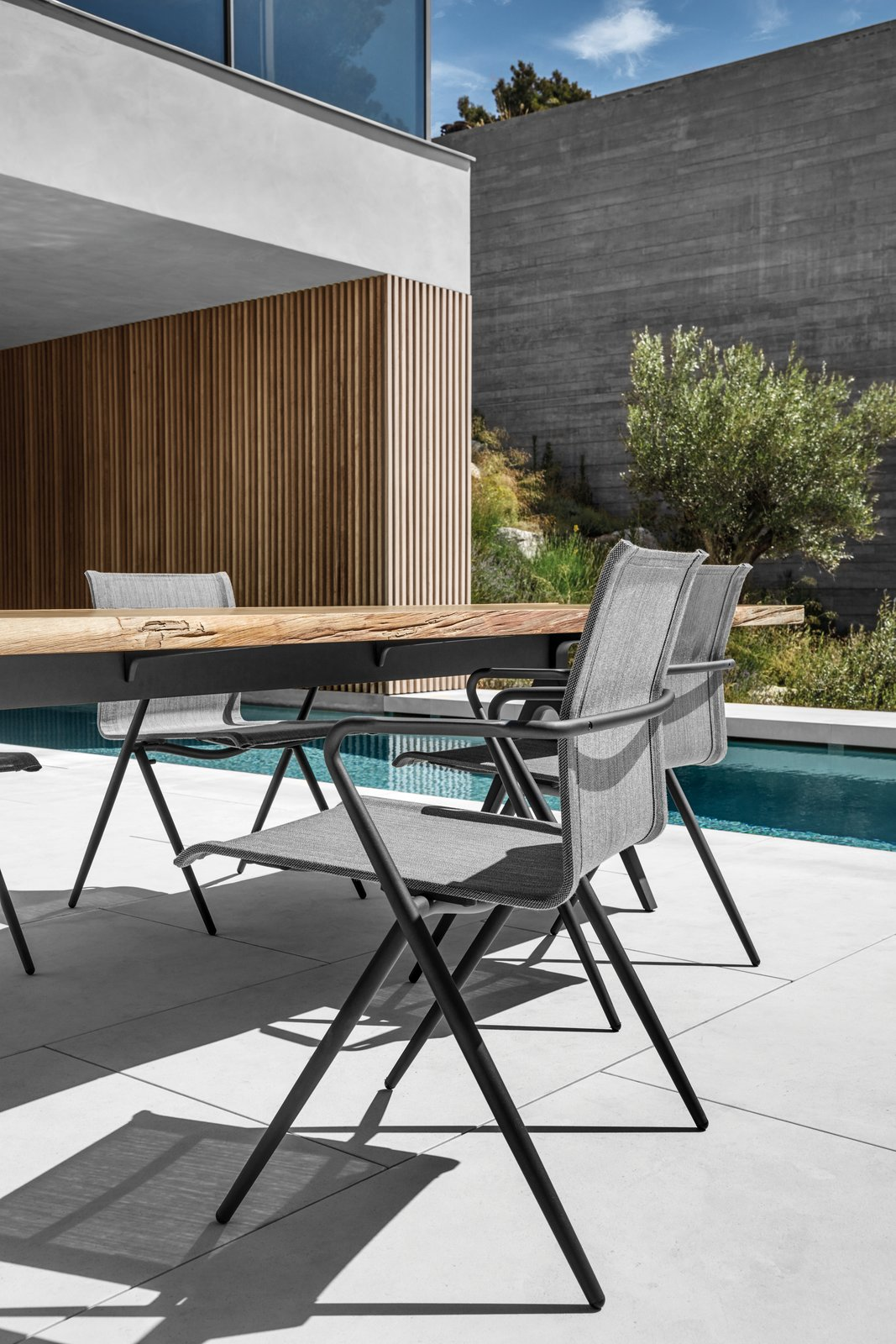 The stackable Ryder dining chair and Split Raw table. Tagged: Chair, Table, Outdoor, Tile Patio, Porch, Deck, Small Pools, Tubs, Shower, Swimming Pools, Tubs, Shower, Trees, Hardscapes, and Back Yard.  Dining Chairs