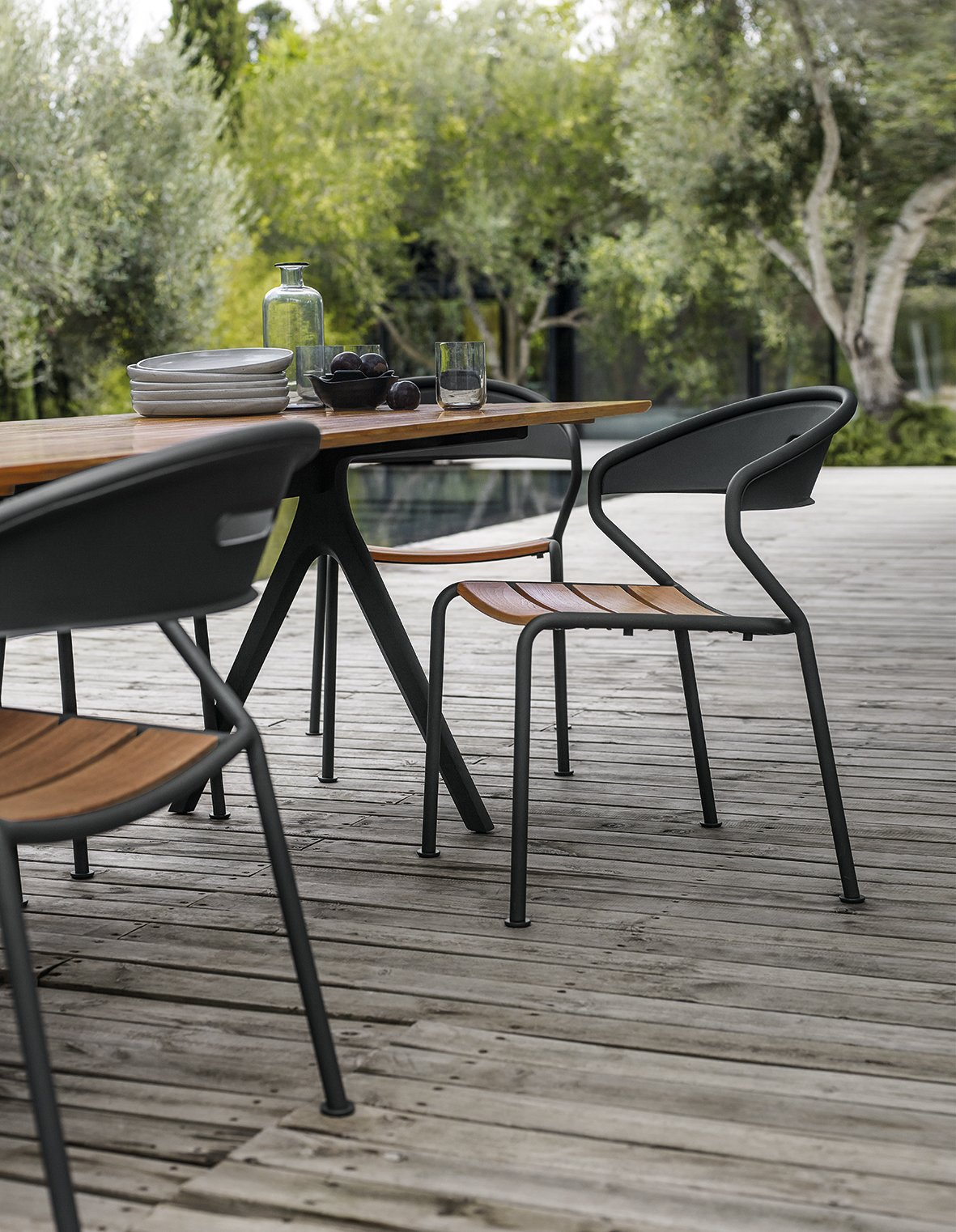 Stackable Curve chair with buffed teak in color Meteor. Tagged: Table, Chair, Outdoor, Large Pools, Tubs, Shower, Large Patio, Porch, Deck, Small Patio, Porch, Deck, Small Pools, Tubs, Shower, Swimming Pools, Tubs, Shower, Wood Patio, Porch, Deck, Trees, Back Yard, and Hardscapes.  Dining Chairs by Gloster Furniture