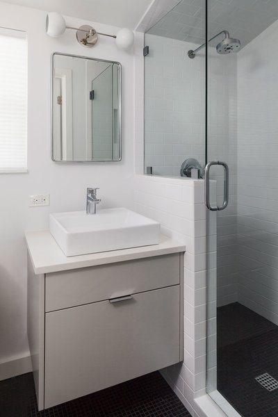 This small en suite bathroom features a floating vanity and black marble mosaic flooring throughout. We love the stark contrast between the flooring and the other materials in the room. Photo 12 of St. Johns House modern home