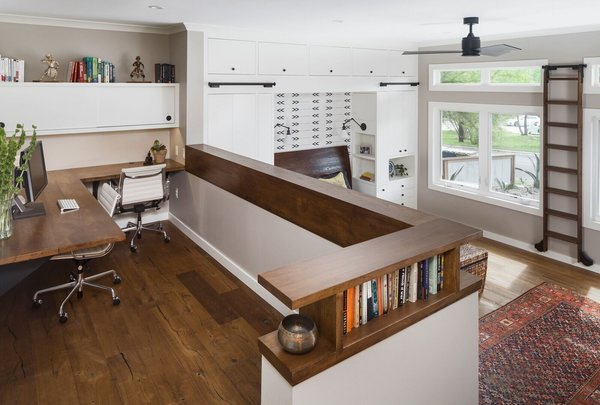We created a platform at the entry of the bedroom so you could walk into the room at the same level as the rest of the house. Creating this platform allowed easy access to the new home office location and master bathroom. Prior to the remodel you had to walk down the stairs into the bedroom and up more stairs to get into the bathroom. This area is accented by a gorgeous floating pecan desk, open shelving that acts as a decorative railing, and an original brick wall that we discovered during construction.  Photo 2 of Barton Hills Bedroom modern home