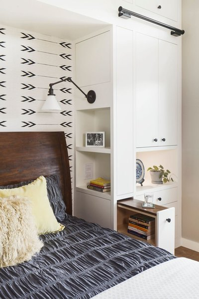 Optimum functionality was important for the bedside built-ins. Clients each a pull out nightstand with adjustable shelves and wood top, open shelves facing the bedside, and articulating sconce with it's own switch. The overall aesthetic is warm, clean and minimal, with white cabinets, stained European white oak floors, and matte black hardware. An accent wall of Cavern Home wallpaper adds interest and ties the finishes of the room together.  Photo 7 of Barton Hills Bedroom modern home