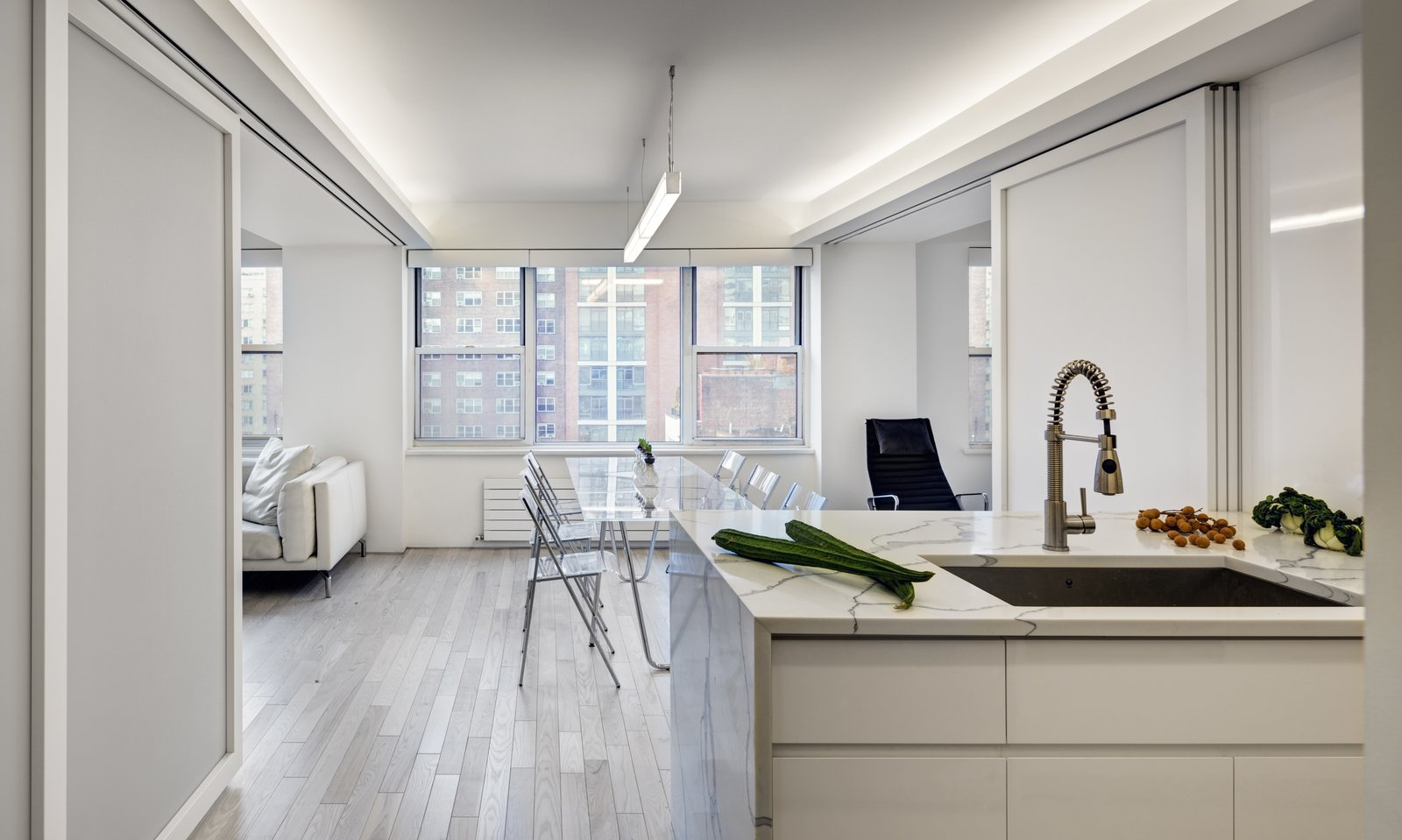 Flex Space: View of Open kitchen and island counter (Sliding panels in open position) Tagged: Kitchen, Ceiling Lighting, White Cabinet, Pendant Lighting, Light Hardwood Floor, Engineered Quartz Counter, and Undermount Sink.  Studio Combination, Murray Hill, NY by Lilian H. Weinreich AIA
