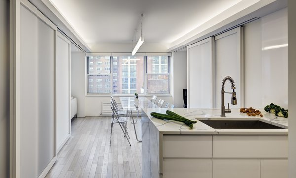 Modern home with engineered quartz counter, undermount sink, pendant lighting, white cabinet, light hardwood floor, recessed lighting, and kitchen. Flex Space: View of Open kitchen and island counter (Sliding panels in semi-closed position) Photo 2 of Studio Combination, Murray Hill, NY