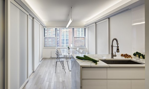 Modern home with engineered quartz counter, undermount sink, light hardwood floor, white cabinet, pendant lighting, recessed lighting, and kitchen. Flex Space: View of Open kitchen and island counter (Sliding panels in closed position) Photo 3 of Studio Combination, Murray Hill, NY