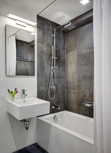 Modern home with white cabinet, recessed lighting, refrigerator, range, range hood, microwave, dishwasher, bath room, porcelain tile floor, wall mount sink, open shower, alcove tub, wall lighting, one piece toilet, and porcelain tile wall. Second Full Bathroom Photo 5 of Studio Combination, Murray Hill, NY
