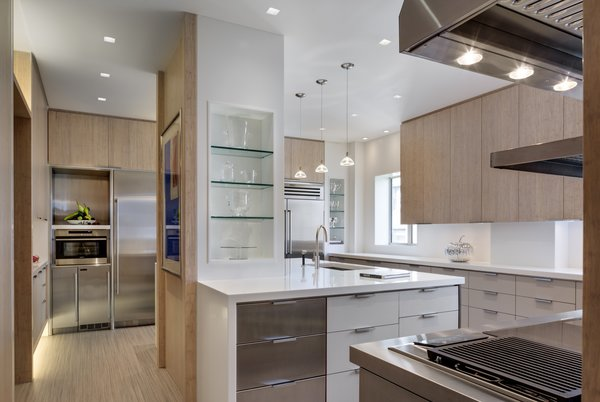 Modern home with kitchen, stone counter, white cabinet, metal cabinet, laminate cabinet, wood cabinet, vinyl floor, stone slab backsplashe, ceiling lighting, pendant lighting, refrigerator, wall oven, cooktops, range hood, ice maker, dishwasher, microwave, wine cooler, and undermount sink. Kitchen  Photo  of State-of-the-Art Central Park Kitchen, NY