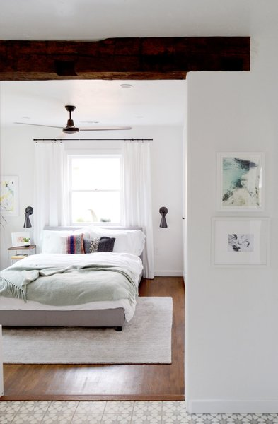 A low profile bed flanked with Cedar & Moss wall sconces lends itself to a simple but practical bedroom space. Photo  of Spenla Master Bed & Bath Open Space Concept modern home