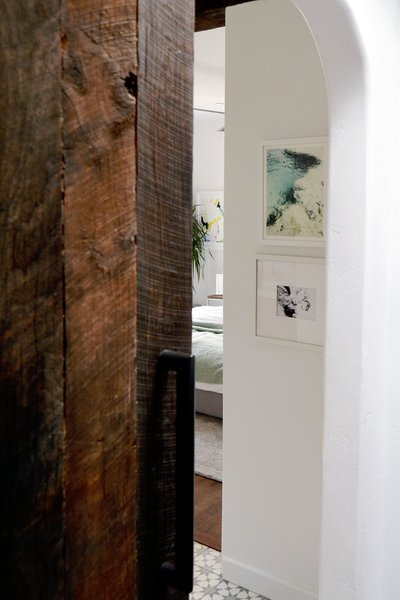 A large handmade (by the owner) rustic barn door divides the room (and shows off a pretty arched door opening) from the rest of the house. Photo 2 of Spenla Master Bed & Bath Open Space Concept modern home
