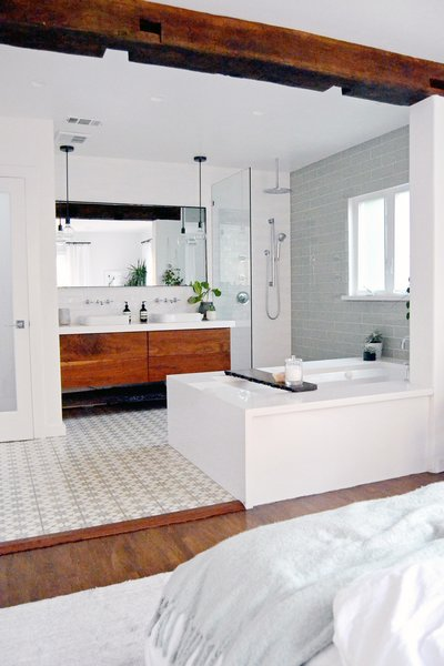 A soaker tub and large reclaimed beam (salvaged from an old barn) creates a casual boundary between bath and bedroom. Moroccan-inspired cement tile, a custom vanity, white quartz Kohler bath fixtures create a spa-like feel. Photo 3 of Spenla Master Bed & Bath Open Space Concept modern home