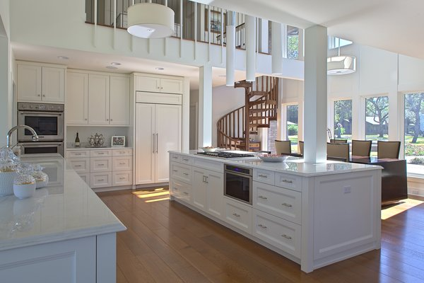 Modern home with kitchen, marble counter, white cabinet, medium hardwood floor, pendant lighting, wall oven, refrigerator, microwave, dishwasher, wine cooler, ice maker, drop in sink, range, and cooktops. Photo 15 of Destin Residence
