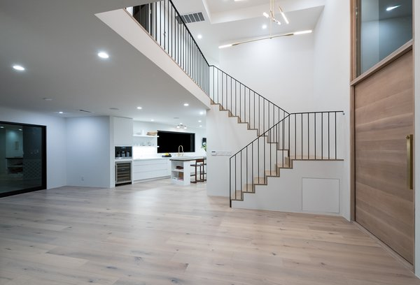 Modern home with marble counter, stone counter, white cabinet, wood cabinet, front yard, stone slab backsplashe, one piece toilet, recessed lighting, wood burning fireplace, coffee tables, wall lighting, bed, night stands, light hardwood floor, and staircase. Photo 10 of The Oaks on Whitman
