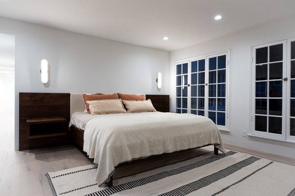 Modern home with marble counter, stone counter, white cabinet, stone slab backsplashe, one piece toilet, recessed lighting, wood cabinet, front yard, wood burning fireplace, coffee tables, wall lighting, bed, night stands, light hardwood floor, and bedroom. Photo 9 of The Oaks on Whitman