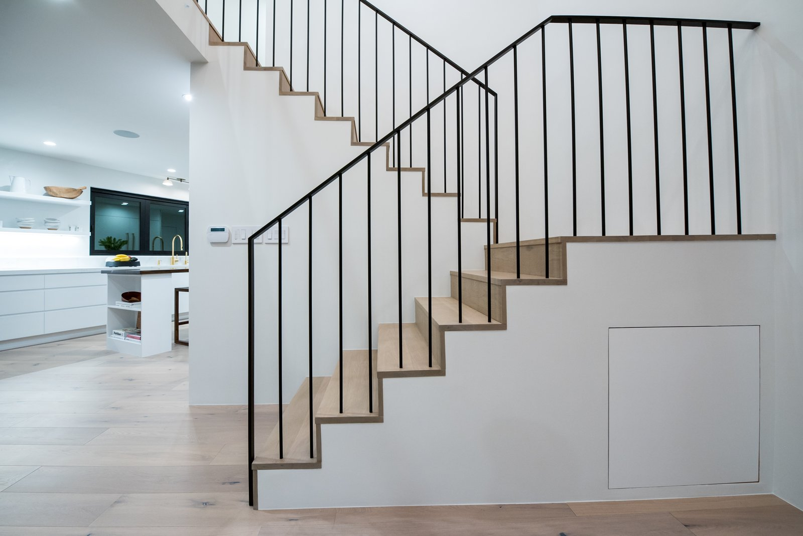 A custom handrail with spindles continuing directly into the treads and landings below allows for a clean minimal look.   The Oaks on Whitman by Landmark Building Inc.