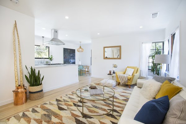 Modern home with horizontal fence, living room, front yard, trees, shrubs, hardscapes, sofa, chair, ceiling lighting, recessed lighting, and light hardwood floor. Photo  of Silverlake on Riverside Terrace