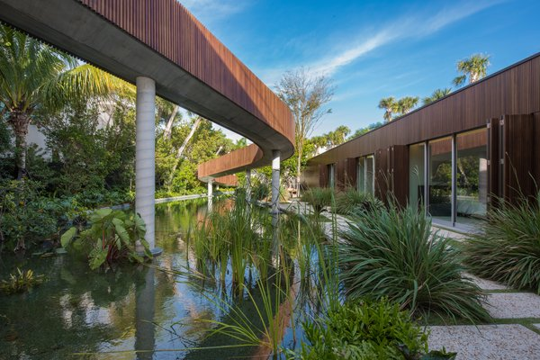 Modern home with back yard, stone patio, porch, deck, infinity pool, large pool, salt water pool, grass, and outdoor. A 200-foot winding  bridge connects the front of the home to the rear. Photo 3 of Pine Tree North