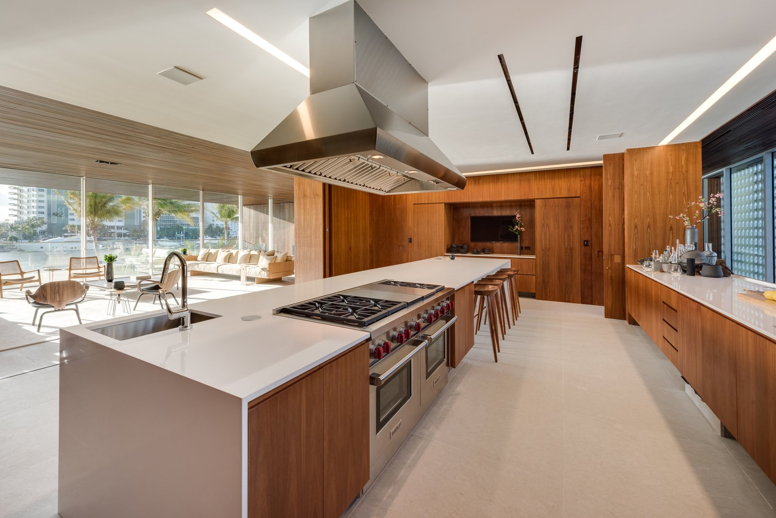 Spacious and bright, the kitchen features a large island with seating and opens up to the living area. Tagged: Trees, Gardens, Concrete, Shrubs, Chair, Sofa, Recessed, Limestone, and Kitchen.  Best Kitchen Recessed Gardens Photos from Pine Tree North