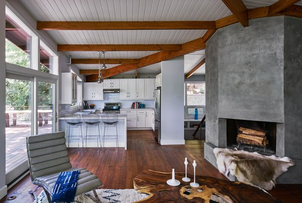 Modern home with marble backsplashe, picture window type, white cabinet, range, range hood, refrigerator, and kitchen. New kitchen expands in all directions - from living room to ipe deck. Photo  of Highland Perch House