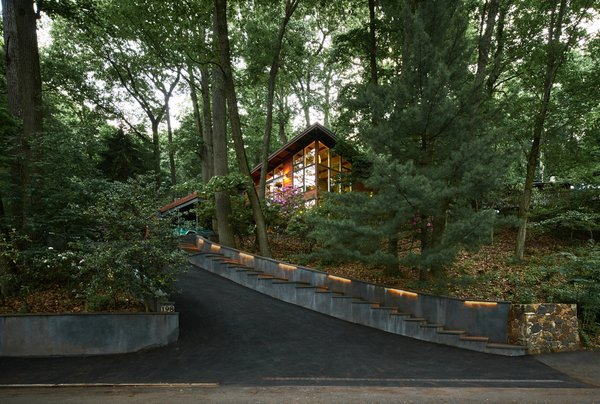 Modern home with trees, hardscapes, storage, picture window type, rooftop, casement window type, outdoor, front yard, shrubs, and walkways. Towering high above the street,  the house glows among the trees. Photo 4 of Highland Perch House
