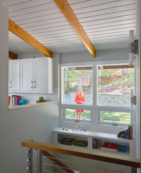 Modern home with storage, picture window type, casement window type, shelves storage type, medium hardwood floor, wall lighting, and hallway. The stairwell brightens up with new openings to the kitchen and enlarged windows to the backyard. Photo 6 of Highland Perch House