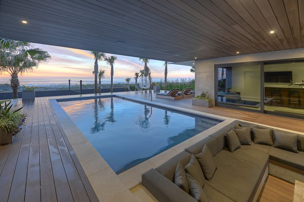 Modern home with outdoor. Covered deck, sunken fire pit, and pool Photo  of Atlantic Beach Modern