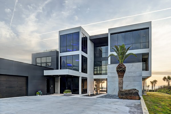 Modern home with back yard, concrete pool, hardscapes, walkways, small pool, large patio, porch, deck, planters patio, porch, deck, decking patio, porch, deck, horizontal fence, swimming pool, grass, shrubs, trees, and outdoor. street facing facade Photo 6 of Atlantic Beach Modern