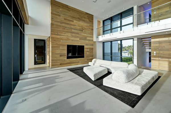 Modern home with hardscapes, horizontal fence, walkways, decking patio, porch, deck, large patio, porch, deck, planters patio, porch, deck, grass, shrubs, trees, front yard, boulders, sectional, bed, night stands, wall lighting, ceiling lighting, engineered quartz counter, ceramic tile floor, concrete floor, and undermount sink. living room Photo 18 of Atlantic Beach Modern