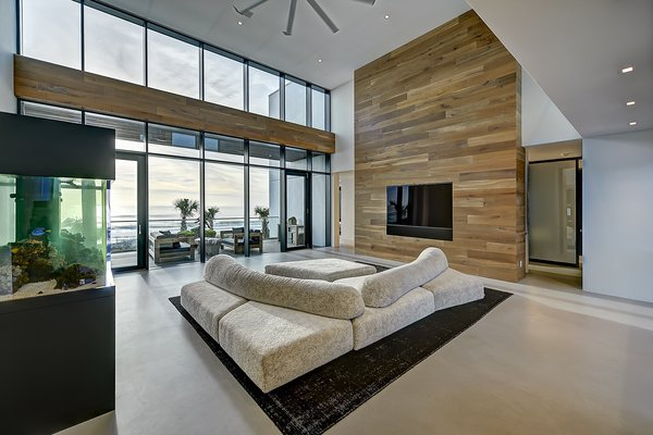 Modern home with hardscapes, horizontal fence, walkways, planters patio, porch, deck, large patio, porch, deck, decking patio, porch, deck, grass, shrubs, trees, front yard, boulders, sectional, bed, night stands, wall lighting, ceiling lighting, engineered quartz counter, ceramic tile floor, concrete floor, and undermount sink. living room Photo 15 of Atlantic Beach Modern